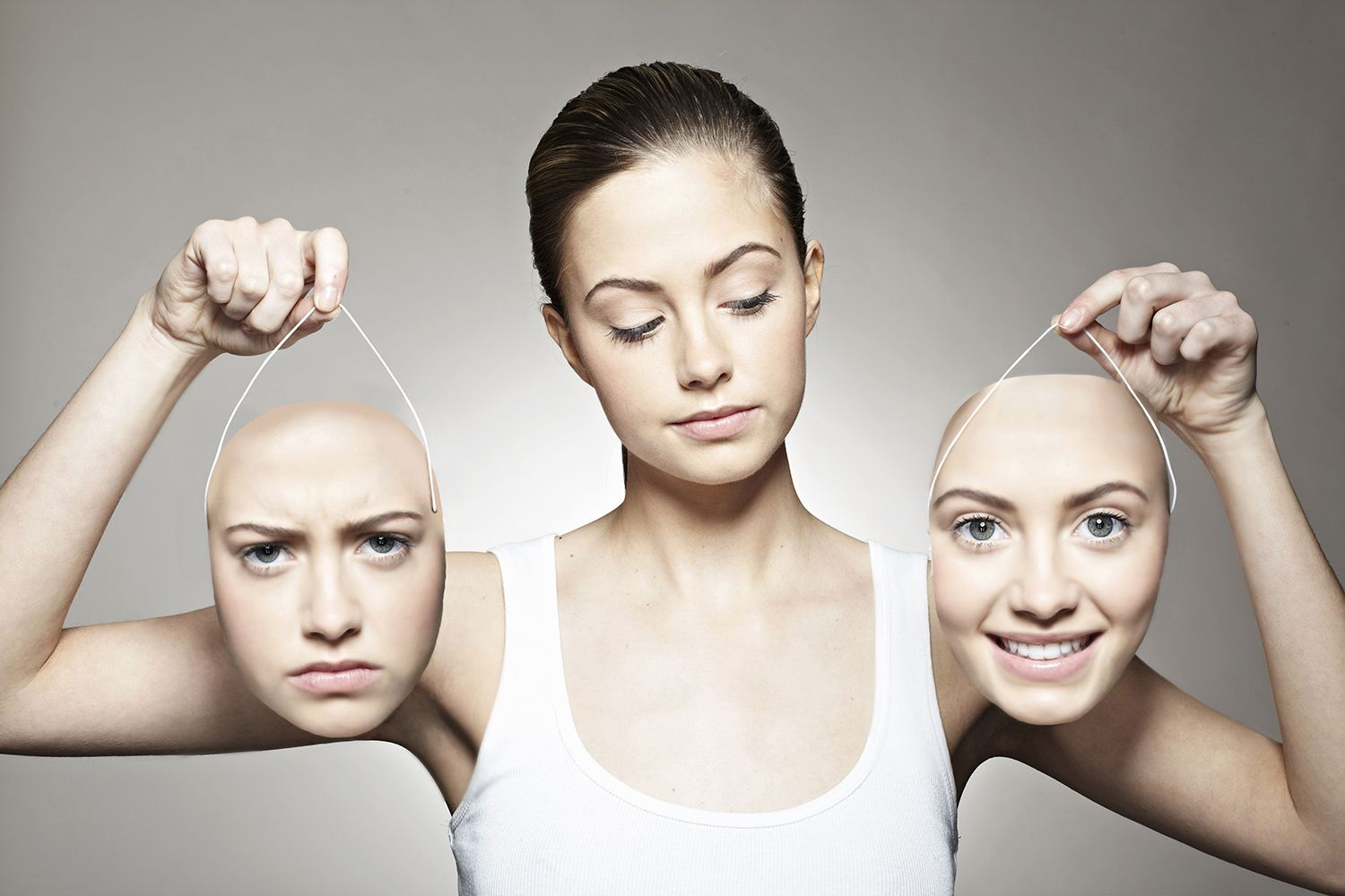 Young woman holding positive and negative emotive masks, looking toward the positive one