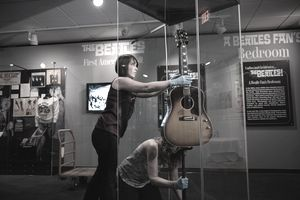 "Museum staff install John Lennon's Gibson J-160E guitar in the traveling exhibit ""Ladies and Gentlemen...The Beatles!"""