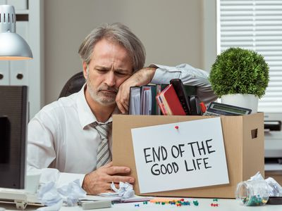 Disgruntled person at office desk with box of belongings whose job was terminated for cause.