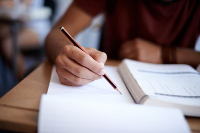 Young man's hand holding a pencil next to book tudying