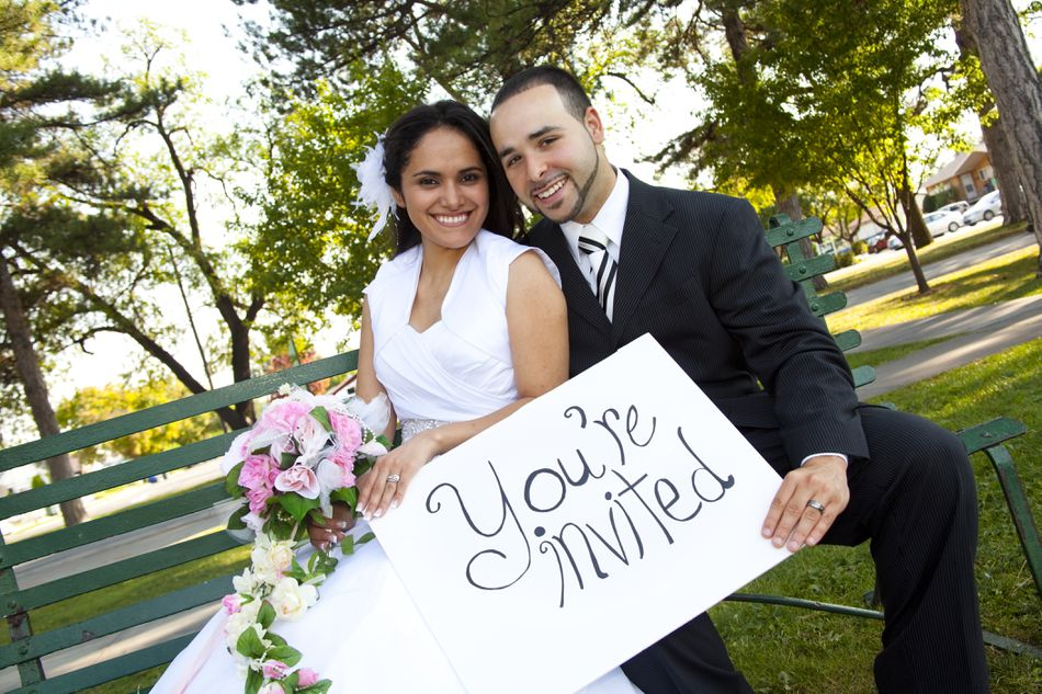 Bride and Groom outside with sign reading You're Invited