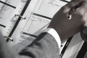 Close up of man writing in a day planner representing time management.
