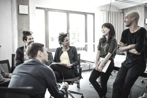 Colleagues looking at cheerful businesswoman in meeting