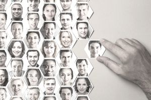 Grid of hexagonal portraits of people with a hand adding new person.