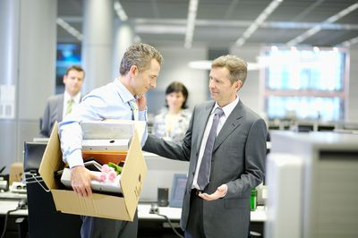 Businessman leaving office with box of personal items after resigning from his job.