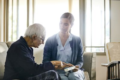 Female caregiver discussing with elderly man