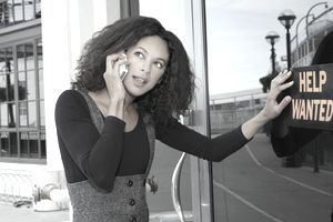 Young woman using a smartphone outside of a building with a