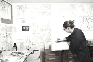 Female artist measuring her painting dimensions of her artwork