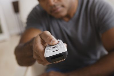 A man pointing a TV remote control