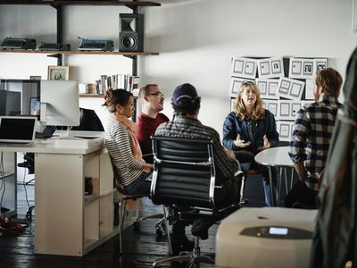 Businesswoman leading meeting in startup office
