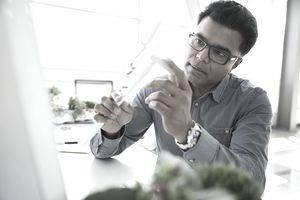 Engineer examining wind turbine model in laboratory