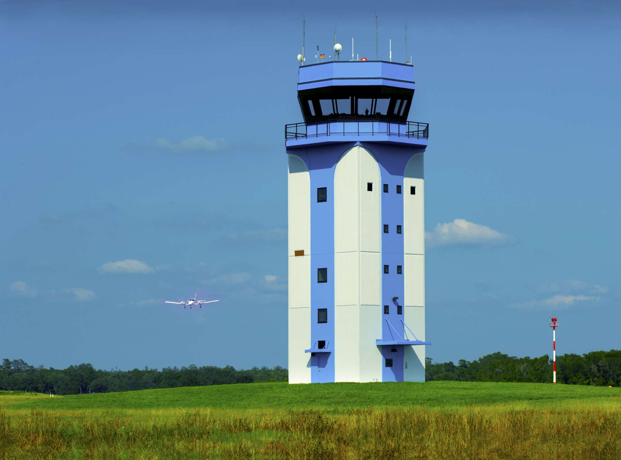 Airport control tower and a commuter plane preparing to land on the runway.