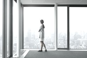 Businesswoman standing in large conference room and looking out of windows