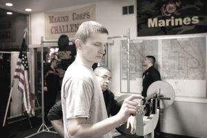 U.S. Marine Corps recruit standing on a scale to ensure he meets height and weight requirements.
