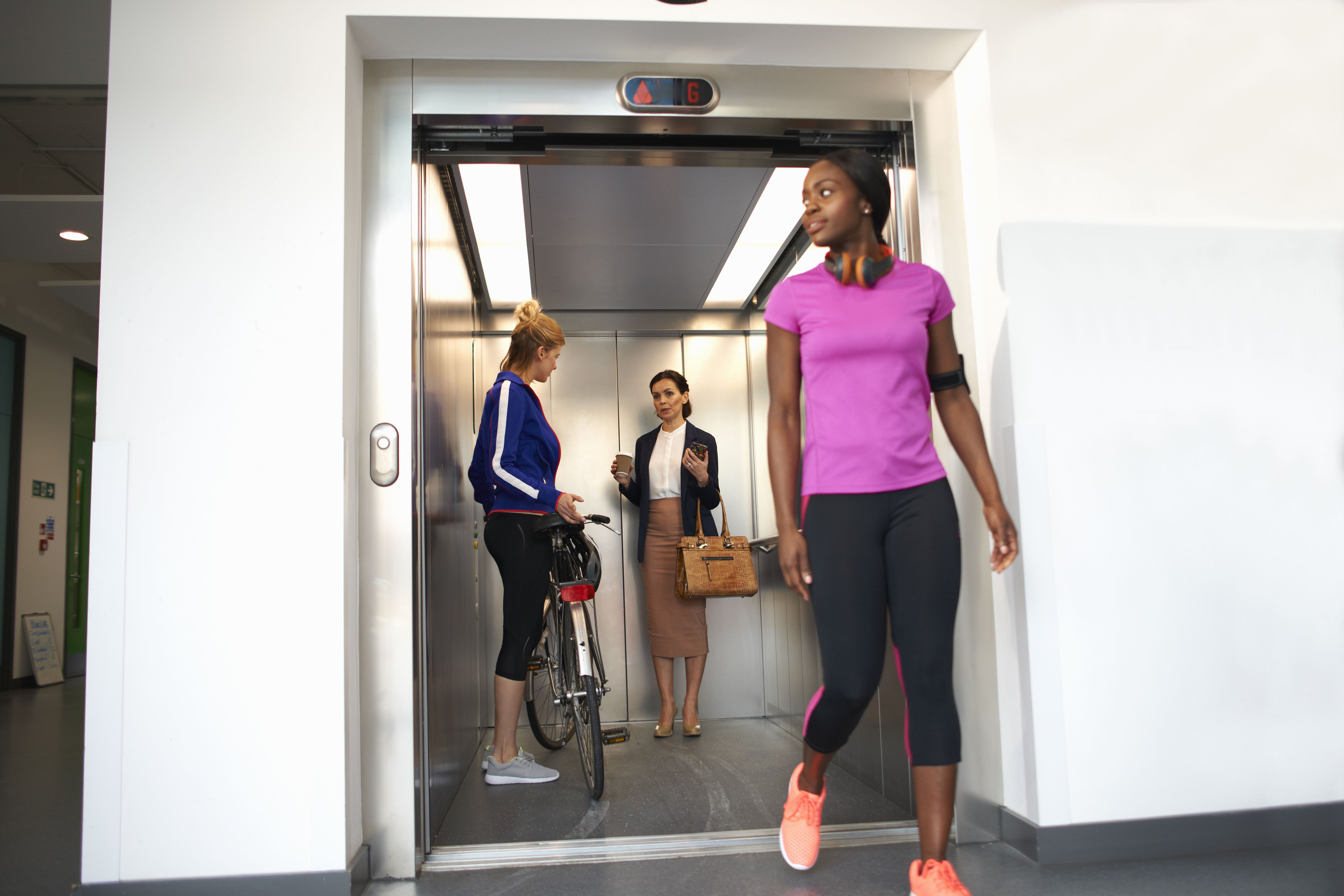 Female colleagues taking office lift