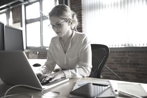 Businesswoman working at laptop at office desk