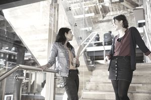 Two colleagues chat on stairs in a modern office
