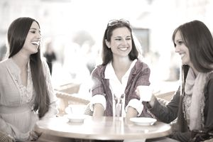a trio of young women having coffee and chatting