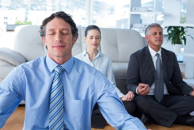 Professionally dressed employees meditating in a company lounge