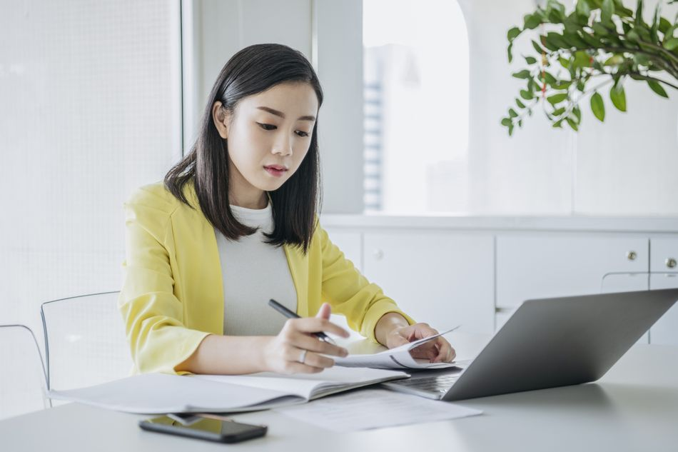 Woman sitting at desk with laptop writing