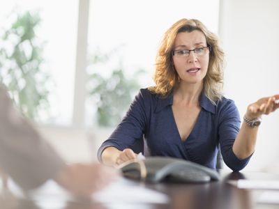 Woman sitting at table speaking during a conference call.
