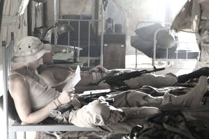 Soldier reading over letter of instruction in the barracks.