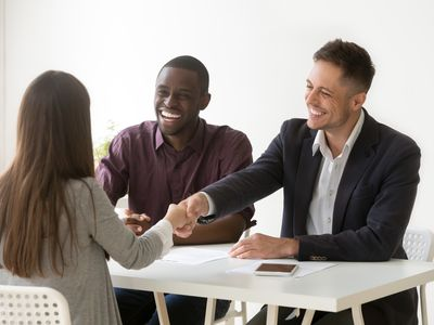 Smiling HR managers with a female applicant at a job interview where they will ask questions to assess her decision making skills.