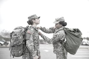 Female Soldier Helping Another Soldier with Shirt