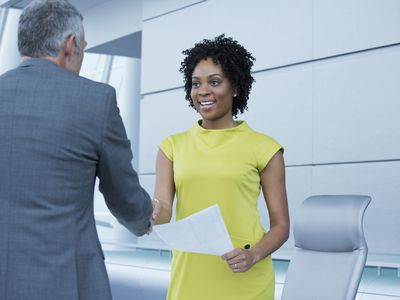 Woman shaking hands with a man at a job interview.