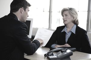Businesswoman and man talking across desk