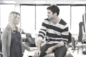 A woman and a man talking in an office.