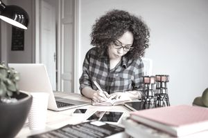 Woman in a home office taking notes