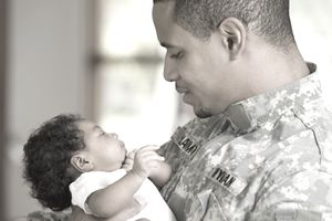 Returning African soldier holding newborn baby