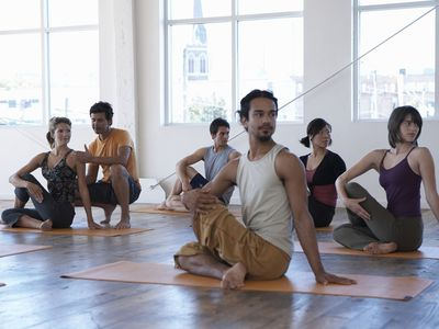 Male yoga instructor teaching class of five adults