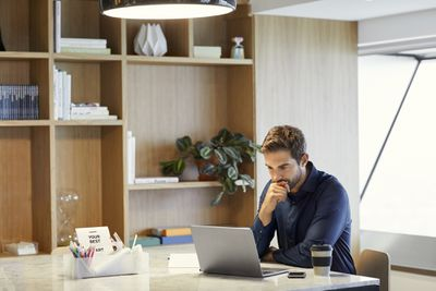 Serious businessman using laptop at office desk