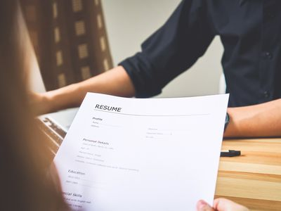 A hiring manager holding a resume while employee conducts a employment history review in the background.