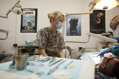 Dentist in military clothing looking over a patient