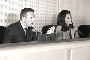 Two people on a dais, one talking into a microphone