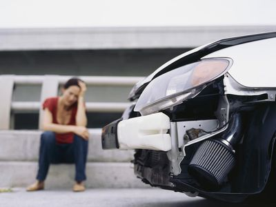 Woman sitting on curb with head on her hand after an accident and before filing an insurance claim.