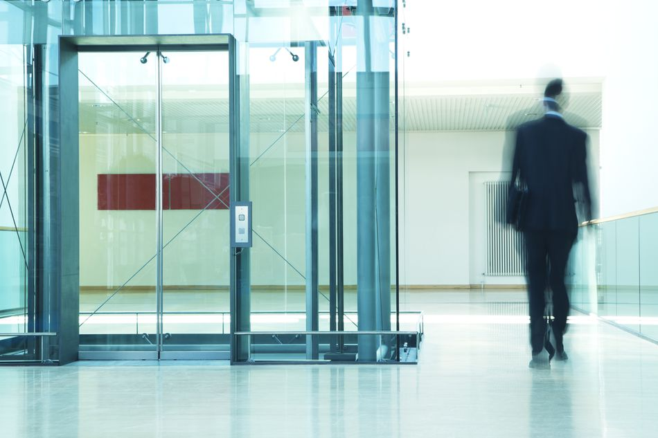 Businessman Walking Past Elevator in Modern Office Building, Motion Blur