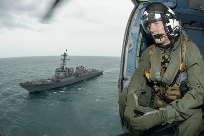 AT SEA, INDONESIA - JANUARY 06: Naval Aircrewman 2nd Class Cody Witherspoon, assigned to Helicopter Maritime Strike Squadron (HSM) 35, keeps a lookout on January 6, 2015 in the Java Sea. The U.S. Navy is supporting the Indonesian-led AirAsia flight QZ8501 search efforts. AirAsia announced that flight QZ8501 from Surabaya to Singapore, with 162 people on board, lost contact with air traffic control at 07:24 a.m. local time on December 28.