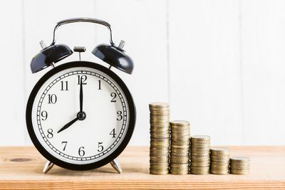 Close-Up Of Alarm Clock With Coins On Wooden Table