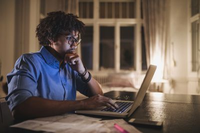 Focused black student working on his laptop computer