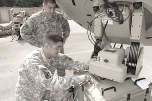 A pair of army IT specialists fixing equipment