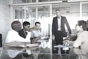 Manager standing at a conference table overseeing a meeting with his staff
