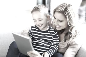 Cheerful mother and son using digital tablet