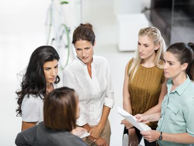 Group of 5 employees talking in a circle to come up with a consensus decision