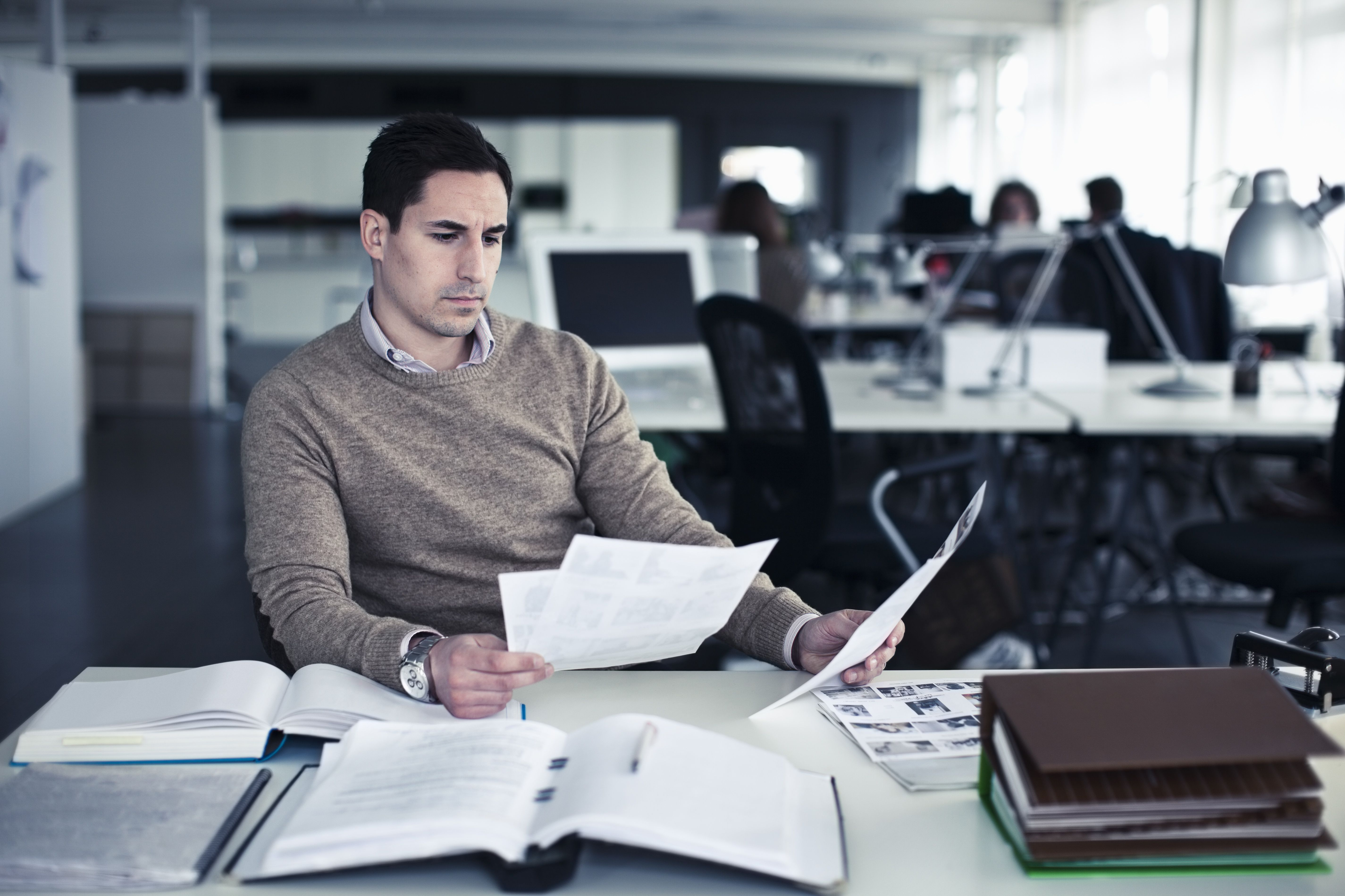 Businessman working at desk looking for red flags on an applicant's resume.