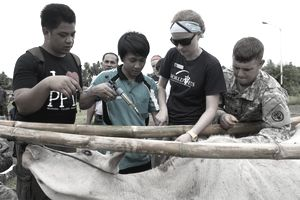 Army Spc Bradley McWillie, right, and World Vets volunteer Helle Hydeskev, work with a local Indonesian veterinarian to administer inoculations to a cow during a veterinary civic actions project, Sangihe, Indonesia