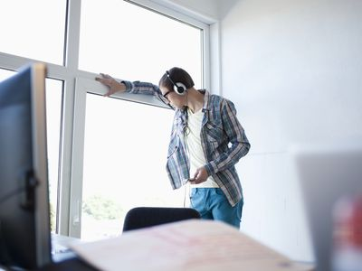 Music supervisor listening to music snippets on headphones while standing in the office by the window.